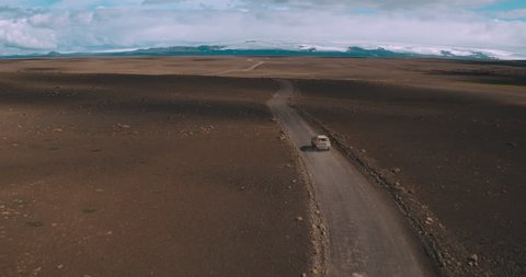 Aerial shot of 4x4 SUV car driving through isolated dirt road in mountain landscape