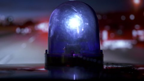 POV driving vehicle with blue flash emergency light on highway at night. Rotating warning beacon mounted on car roof closeup.