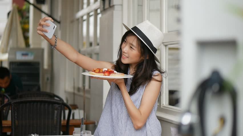 Beautiful asian woman taking selfies on a smartphone. Young asian girl take photo with pancake at cafe shop.