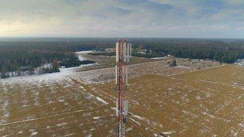 Aerial view of the big field with the GSM 4G 5G glas micro fibre communications tower in the center and few white snow on the ground