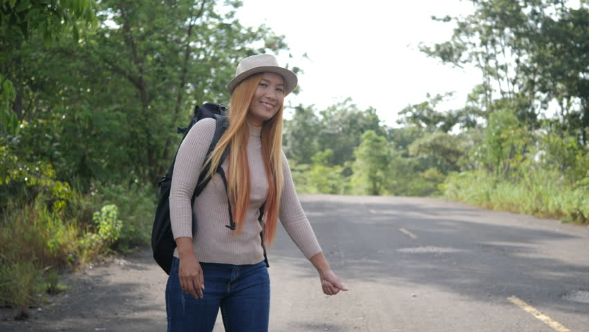 Traveler woman backpacker hitchhiking on the road and walking. #1014915628