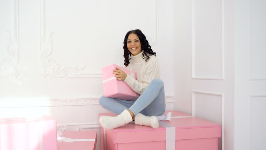 Young cute teen girl holding pink Christmas present. She is dressed in  jeans and white warm sweater. Woman sends an air kiss.
