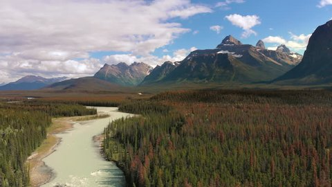 Banff National Park aerial view, flying over the Bow River and lush pine tree forest in the Canadian Rockies, Alberta, Canada.