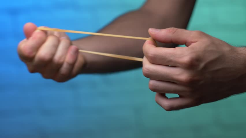 Stretching an elastic rubber band to its limit and breaking it. | Shutterstock HD Video #1014936058