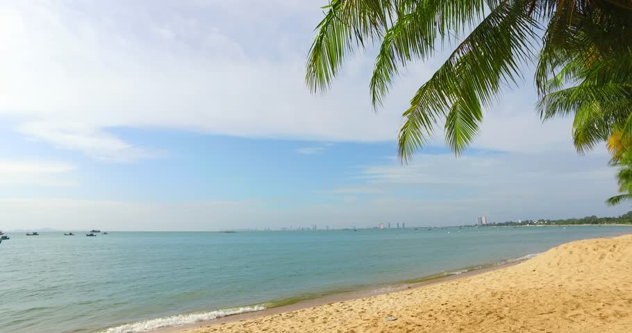 Coconut palm trees on the beach in Thailand. Beautiful beach, Bang Saray beach in CHONBURI, THAILAND. Coconut trees with blue sky for beautiful beach concept. Free space for text. Handheld movement 4K | Shutterstock HD Video #1014945568