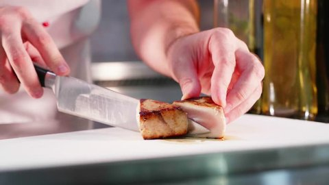 Chef is garnishing fried marlin fish fillet at restaurant kitchen in slow motion. Cook in gloves slicing juicy fish, concept shot.