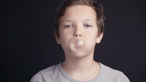 Footage boy make bubble with chew on dark background. 4k video