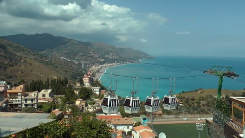 TAORMINA-May 2nd,2018-Cable car coming to Taormina, with beautiful bay in the background-May 2nd,2018