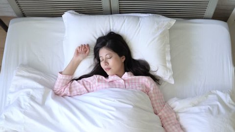 Asian woman opened her eyes slowly and outstretched her arms getting ready to embrace the pleasant Sunday morning.