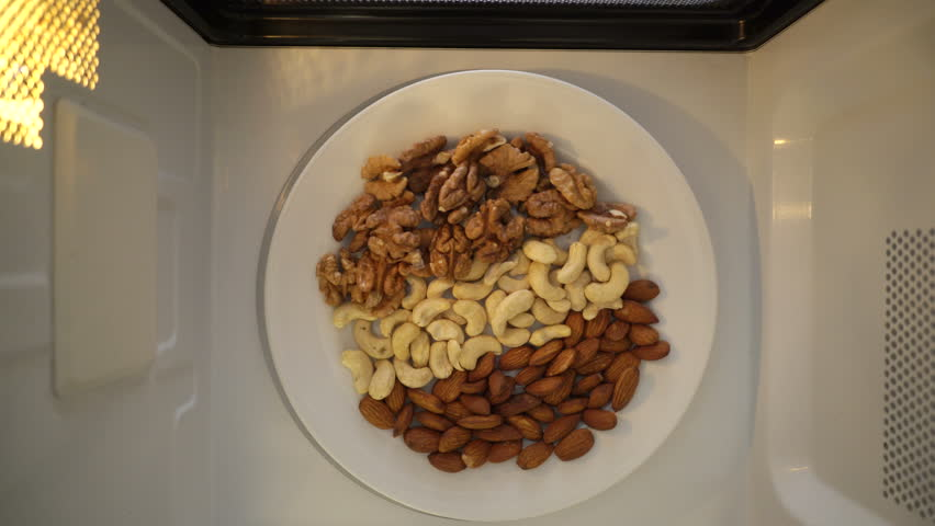 Toasting nuts using microwave. Roasted mixed nuts on a plate spins inside oven. Cashews, walnuts and almonds microwaving.