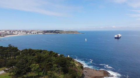 "Santander, Cantabria, north Spain. Peninsula ""La Magdalena"", coast, trees, huge ship, cargo, sail, buildings, aerial view. Spain by drone 4k."