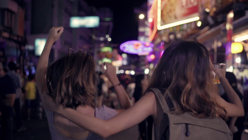 Slow motion - Traveler backpacker Asian women lesbian lgbt couple dancing together. Female drinking alcohol or beer with friends and having party at The Khao San Road in Bangkok, Thailand. #1015004398
