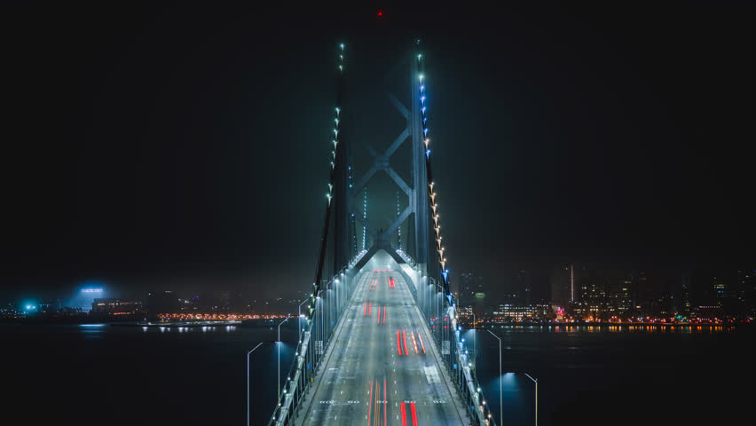 Bay Bridge at night with the illuminated light from cars. Time-lapse. San Francisco city, California, North America, USA