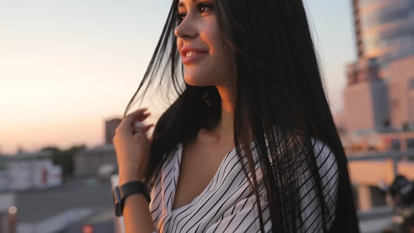 Pretty attractive young woman portrait on rooftop in sunset time