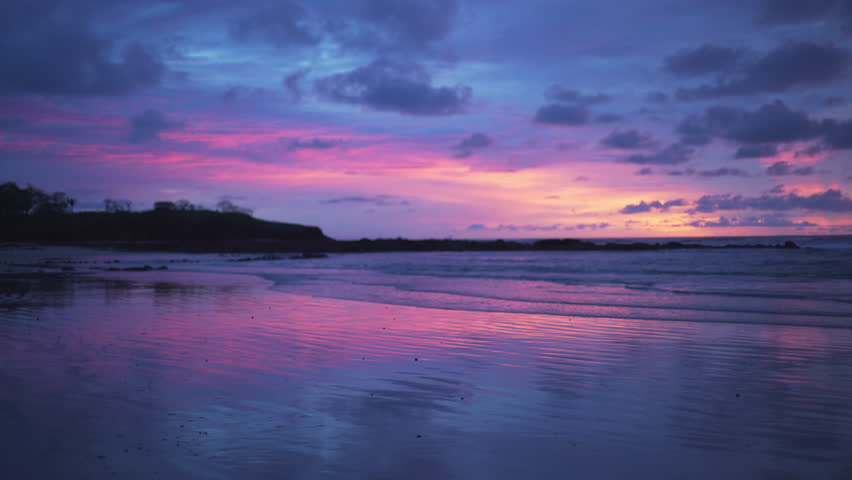 Gorgeous out of focus background plate of purple and blue sunset on the beach in Costa Rica for compositing or keying. Blurred or defocused shot of ocean sun set for green screen composite. 4k
