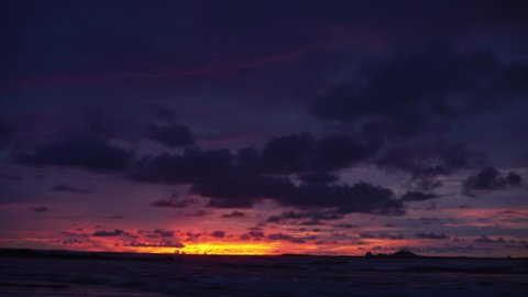 Out of focus background plate of beautiful purple and orange sunset on the beach in Costa Rica for compositing or keying. Blurred or defocused shot of ocean sun set for green screen composite. 4k