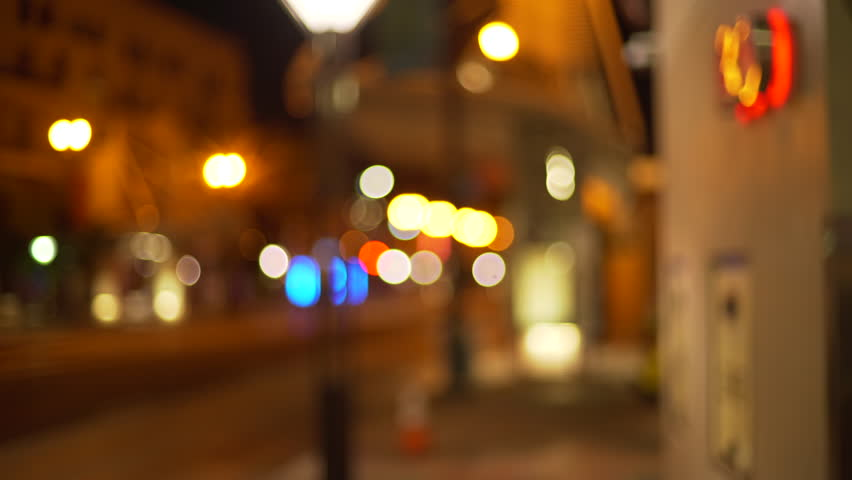 Out of focus background plate of city street from sidewalk at night. Blurry Video backdrop in urban area with bokeh lights for green screen compositing. 4k
