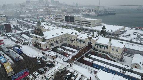 Aerial Above Railway Station Cityscape hills Vladivostok Russia Train historical monument decor symbol Trans-Siberian Railway Port horn Tourist attraction landmark Winter snow overcast Blizzard. Drone