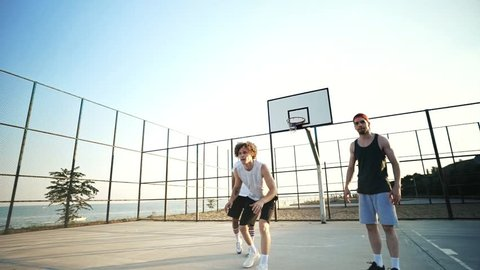 Concentrated four multiethnic friends playing basketball together on playground