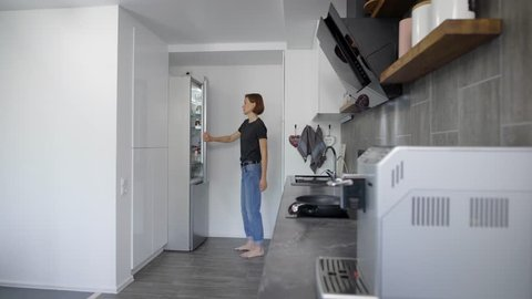 alone young woman is getting eggs from fridge in her kitchen in morning, preparing for cooking breakfast