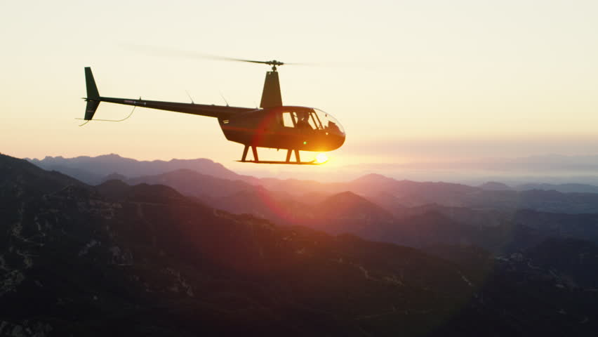 Aerial view of a helicopter flying over mountains in Los Angeles at sunset. Shot with a RED camera. 4k footage.
