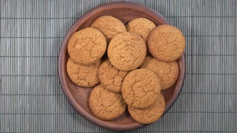 Plate full of oatmeal cookies being snatched up by five hungry children girl. Close up, top view, macro