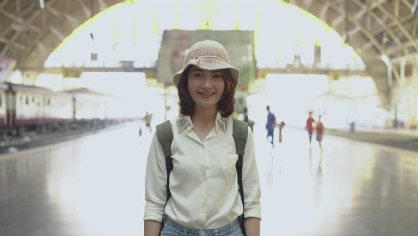 Happy Asian woman waiting the train at train station for travel in summer. Travel Thailand concept. #1015090198