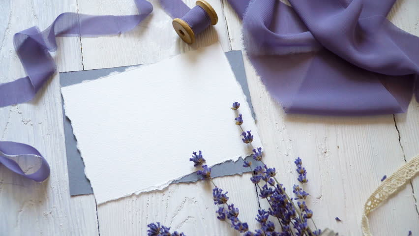 White blank card, envelope and ribbon on a background of pink and blue fabric with lavender flowers on a white background. Mockup with envelope and blank card. Flat lay. Top view