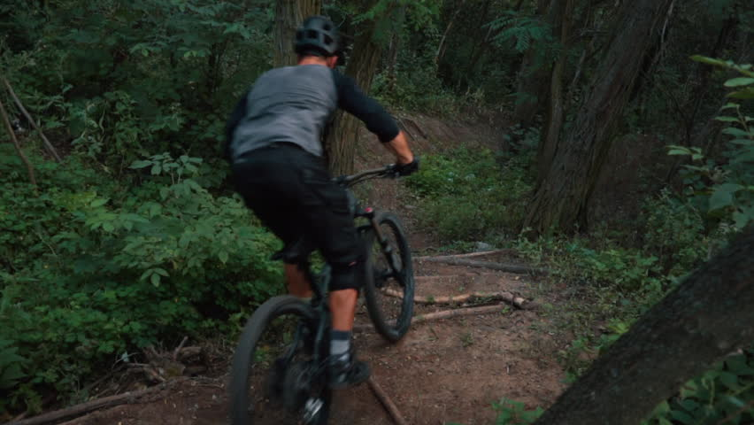 extreme bicyclist rides on forest path, slow motion