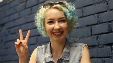 Young woman showing victory sign over blue wall background.