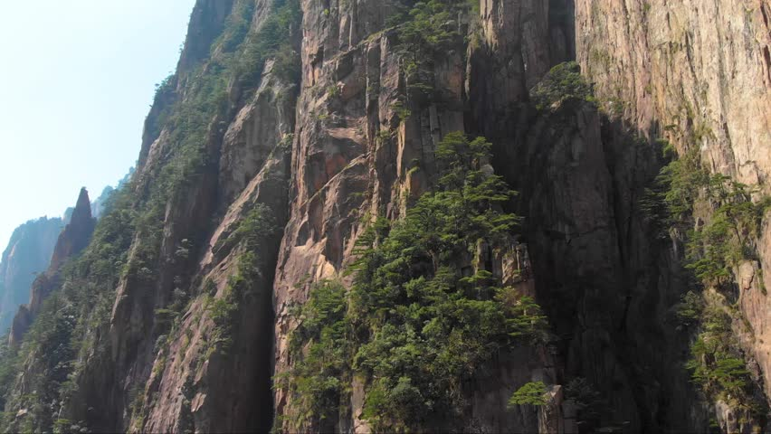 Drone aerial shot rising up over Huangshan mountain in China. Flying epic nature landscape shot of Yellow mountain. Close up of rock formations in famous tourist scenic spot.