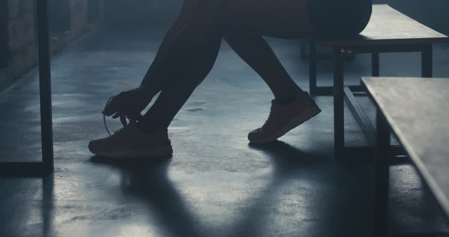 CU DOLLY IN Caucasian female athlete preparing for a workout in a gym locker room, tying shoelaces before training session. 4K UHD 60 FPS SLOW MOTION