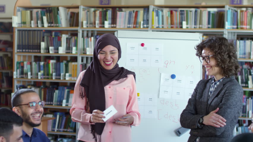 Beautiful muslim woman in hijab standing by flipchart in classroom, smiling and showing word cards to group of migrant students at English lesson with female teacher