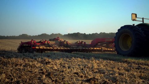 The tractor plows the field with plows before sowing. Tractor plows field agricultural work.