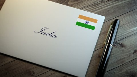 Country name written on a card or envelope in cursive font with a sleek pen on a wooden table surface under beautiful classy light. Stamp in the corner shows the flag of India