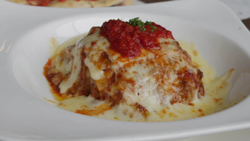 Traditional Italian beef lasagne serving on white plate in restaurant.