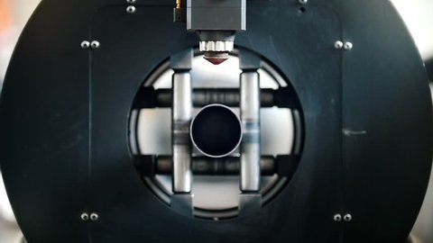 The equipment cuts cylindrical metal, sparks fly from laser