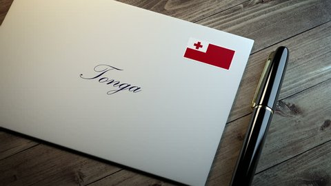 Country name written on a card or envelope in cursive font with a sleek pen on a wooden table surface under beautiful classy light. Stamp in the corner shows the flag of Tonga