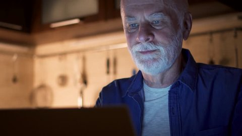 Senior man at home reading news on laptop. Freelancer using computer at night working hard from home-office to meet deadline. Overworked businessman working in kitchen in evening. Camera moving up