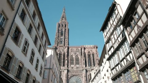 Strasbourg, France - May 4, 2018: Camera dolly forward push in down Rue Merciere lined by traditional Alsatian buildings tilt up to the Cathedral of Our Lady or Cathedrale Notre Dame
