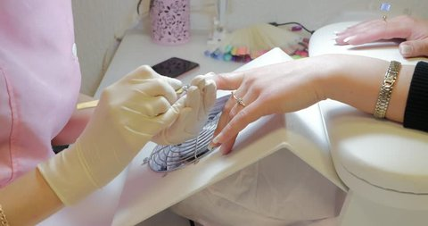 Manicurist using cuticle pusher for pushing cuticles on clients fingers.