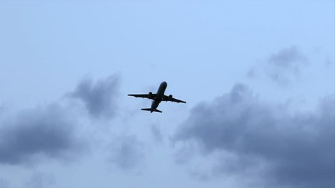 Airplane flying through the cloudy sky. Soaring plane in silhouette with a blue sky background. Modern transportation and aviation. Passenger jet airliner taking off from the airport. Departing flight