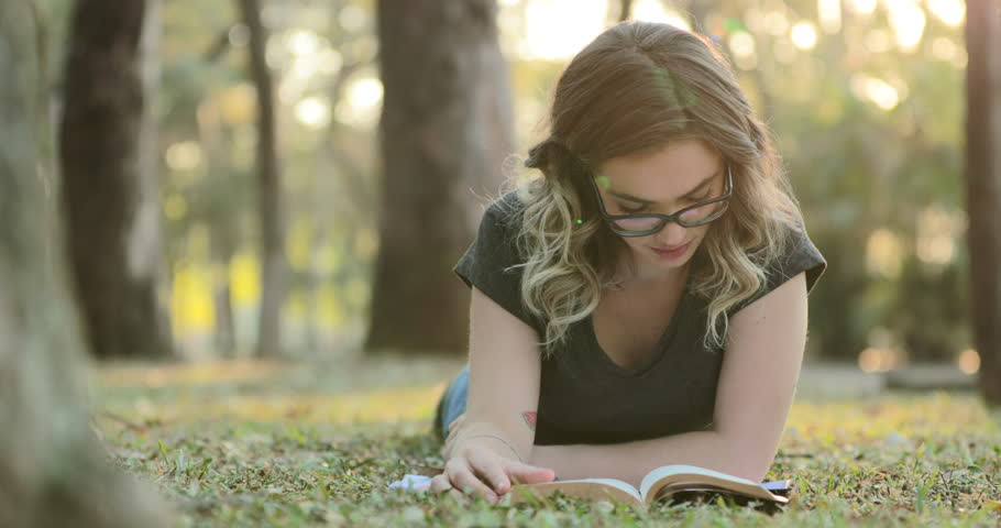 Smart intelligent girl wearing glasses lying on grass outside at the park reading book studying