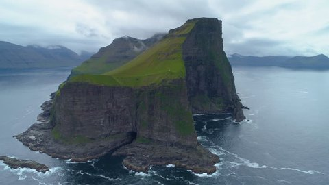 AERIAL: Flying around a grassy islet with black rocky cliffs towering over calm sea on cloudy morning. Spectacular shot of a majestic mountain on small island in the middle of ocean in Faroe Islands.