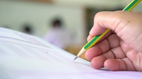 Education students testing exam with pencil drawing selected multiple-choice quizzes or testing exams answer sheets exercises in school, college university classroom