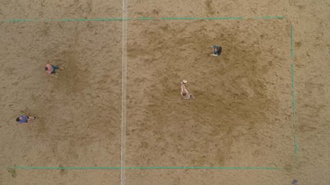 Sportsmans are Playing Beach Volley. Aerial Vertical Top-Down View. Drone is Hovering. Slow Motion