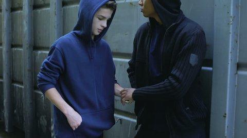 Teenager secretly buying drugs from dealer, disadvantaged city district, crime