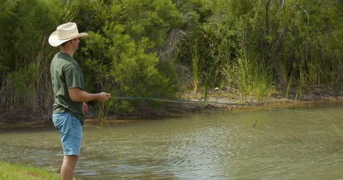 A man wearing a cowboy hat practices his fly fishing from the bank of a  small 06ced59df404