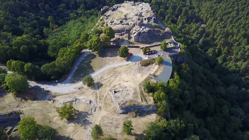 Aerial drone shot big rock formation and castle ruin in coniferous Harz mountains forest landscape / Aerial drone shot big rock formation and castle ruin in coniferous Harz mountains forest landscape