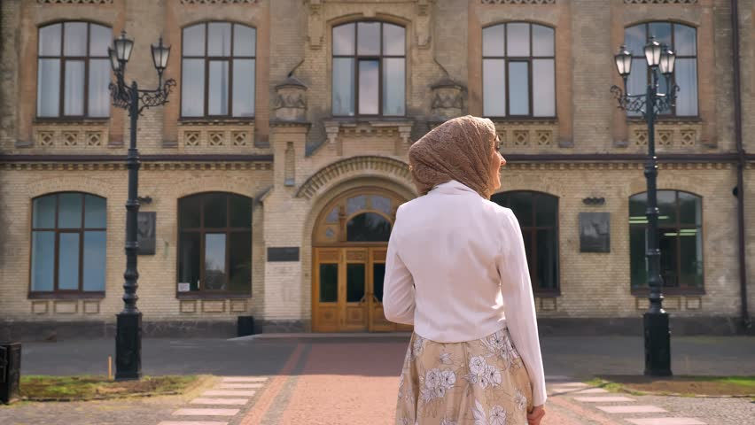 Back view of young muslim woman in hijab walking towards building, looking around, sunny day outdoors